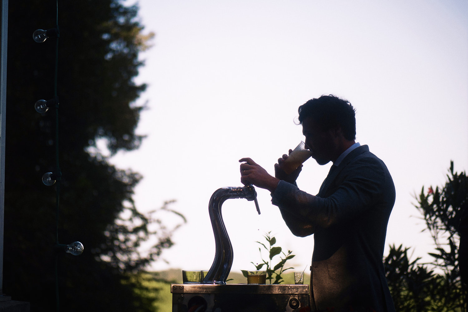 Silhouette of wedding guest drinking from beer tap