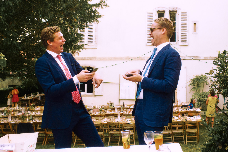 Two men laughing during garden wedding reception