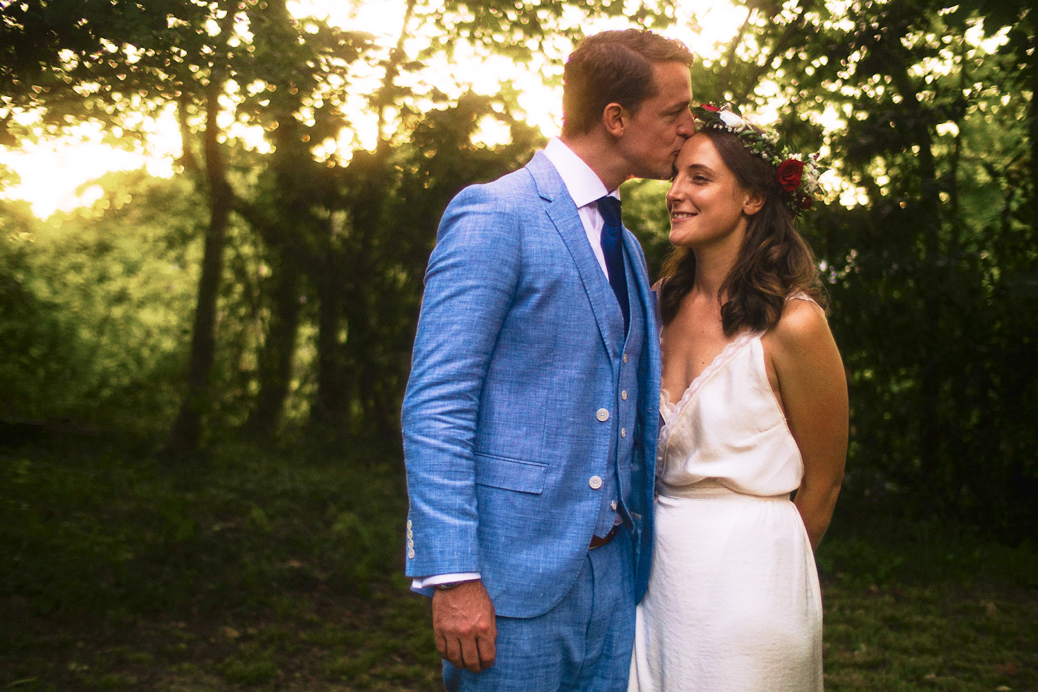 A groom in a blue suit kisses the brde on her forehead in a garden