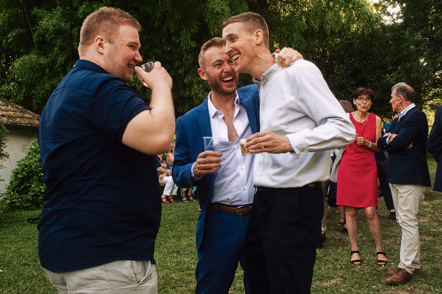 Wedding guests laugh and hug each other in a garden