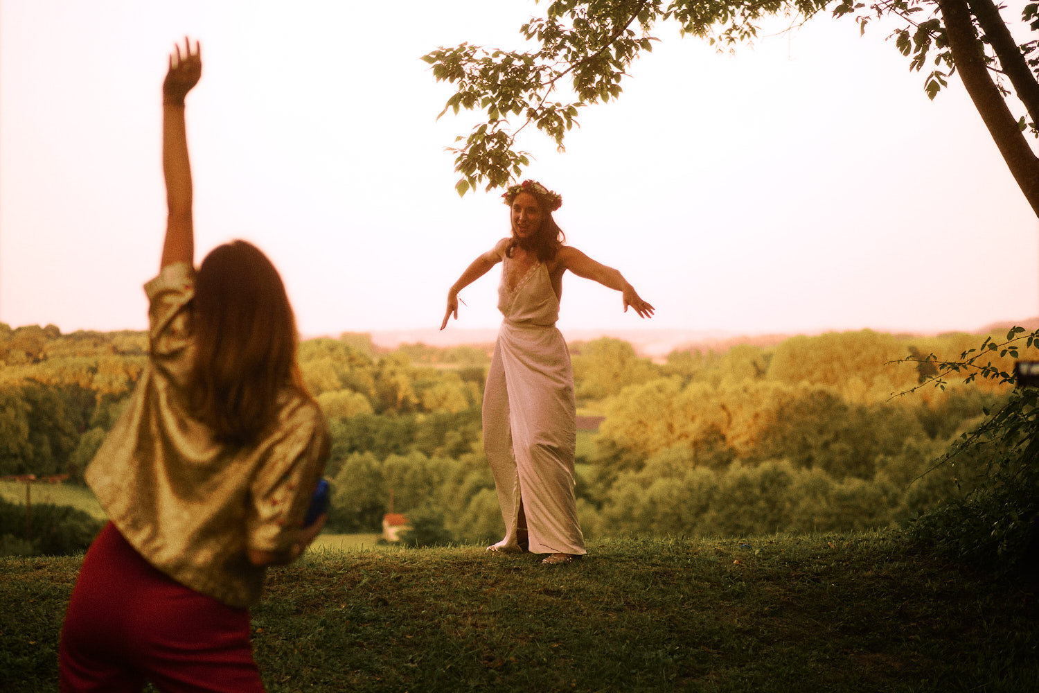 A bride and friend dancing in a garden