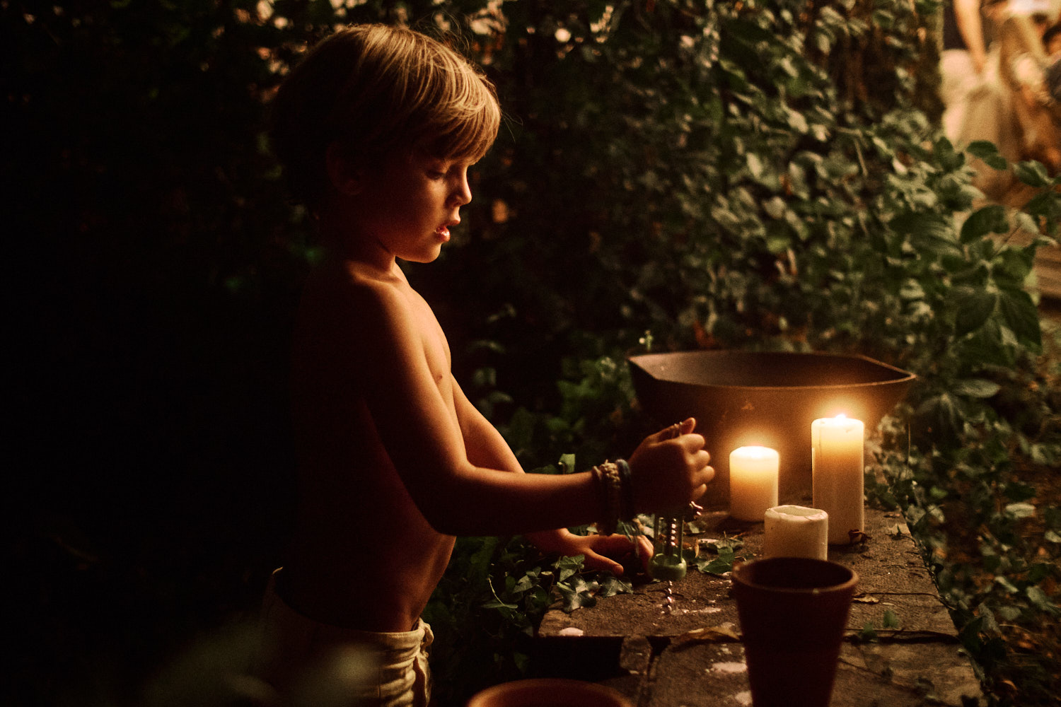 A child is illuminated by candle light at an outdoor wedding reception