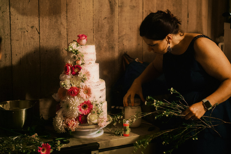 A sister prepares a wedding cake for the bride