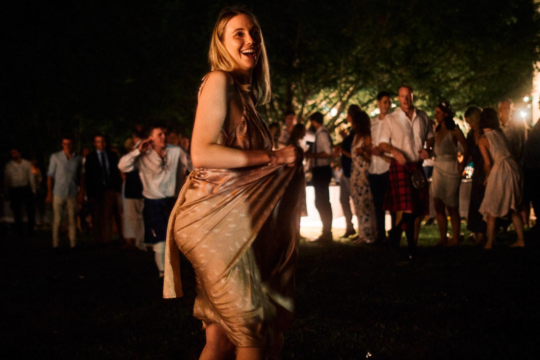 A wedding guest dances outside in a garden