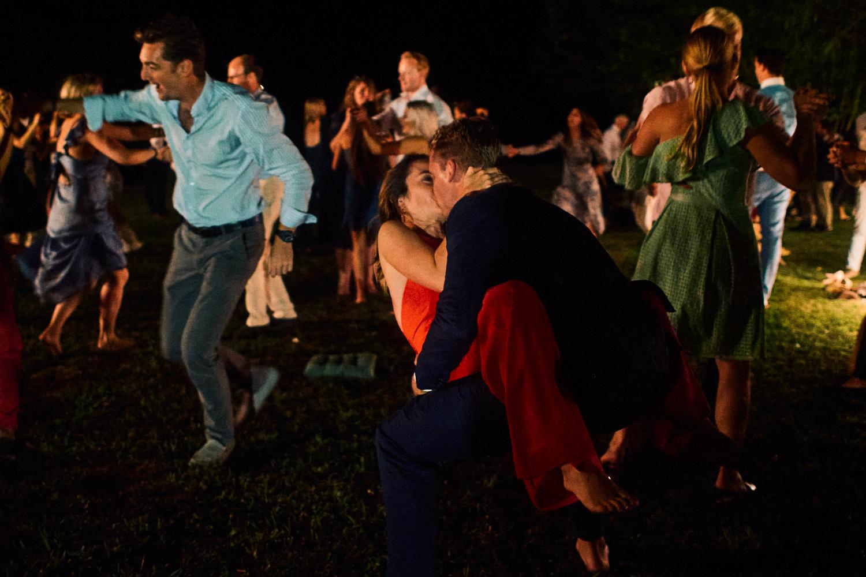 A couple kiss dramatically in a garden at a wedding