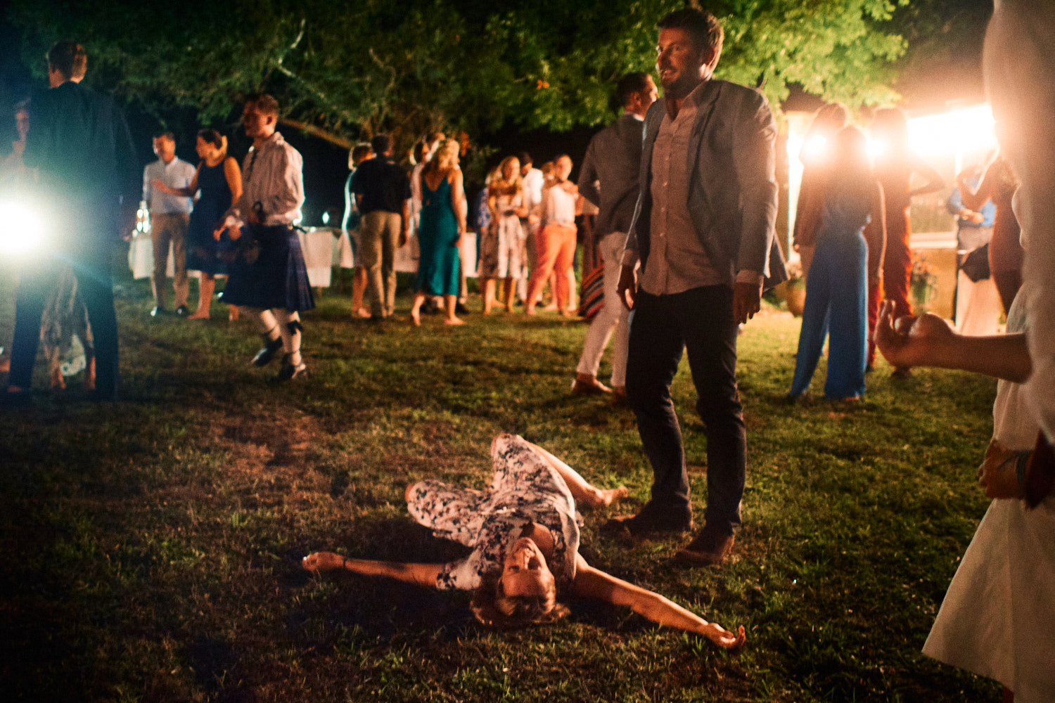 An exhausted dancer lies down on the grass at an outdoor wedding reception