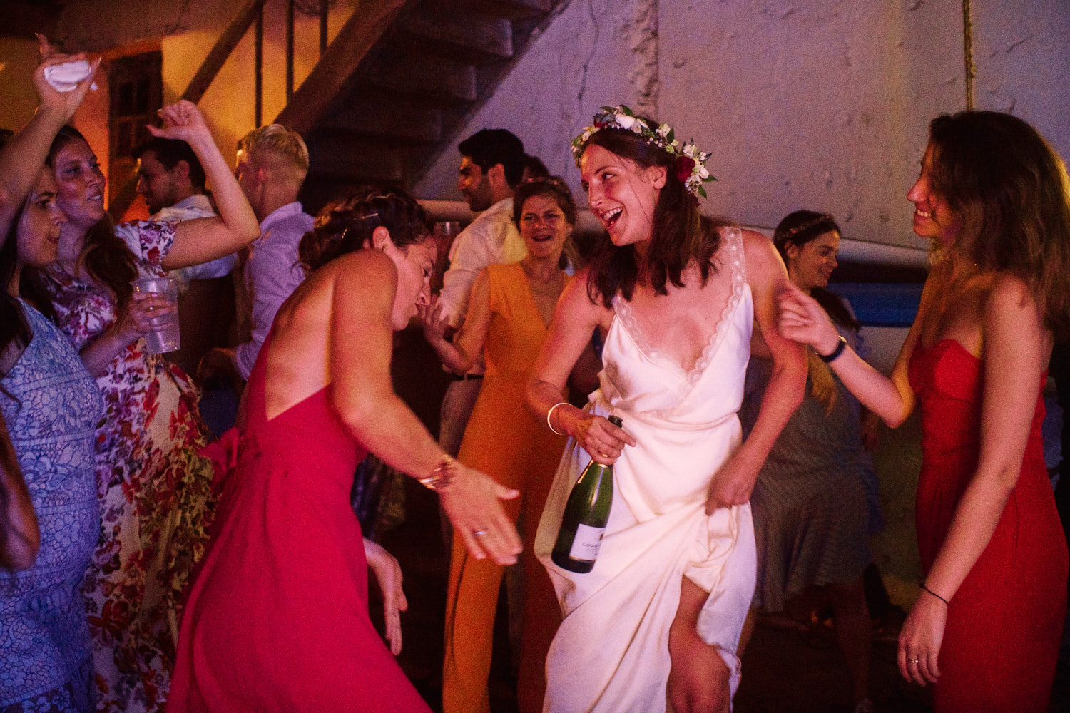 The bride dances with her friends in a barn