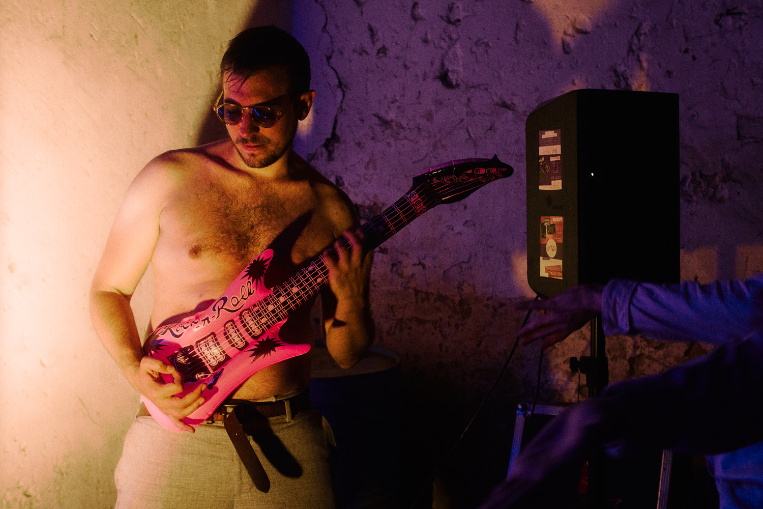 A topless dancer plays with an inflatable pink guitar at a wedding