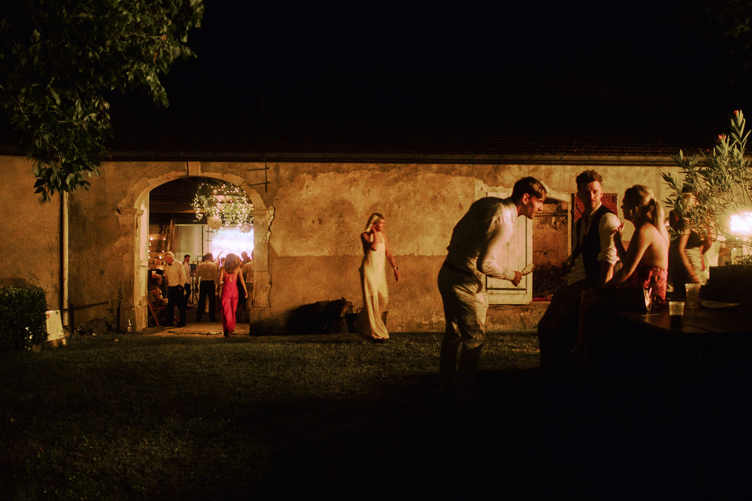 Wedding guests mingle inside and outside a barn at a French wedding