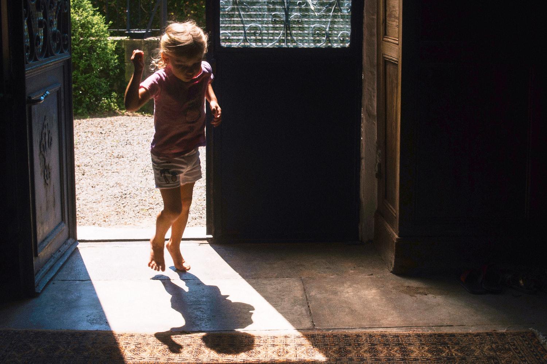 Child in pink t-shirt jumps in doorway